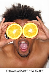 Young man holding halves of oranges in front of his eyes