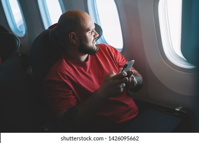 Young man holding in hands cellular feeling comfortable in seat. Smiling male flight passenger connecting to online wireless on board while sitting next to aircraft cabin window. Airplane mode