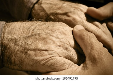 young man holding the hands of an old man