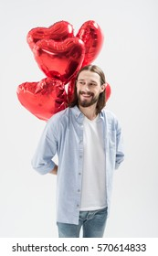 Young man holding heart shaped air balloons and smiling isolated on white