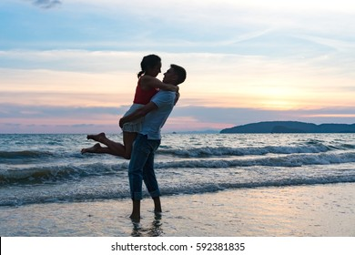 Young man holding in his arms a young woman on the beach against the backdrop of a spectacular sunset