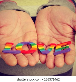 a young man holding in his hands letters painted as the gay pride flag forming the word love, with a retro effect