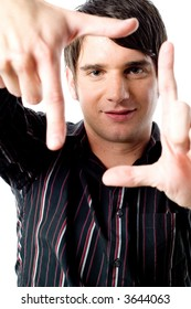 A young man holding his hands up to frame his face on white background