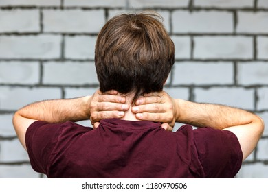 Young man holding his neck in pain