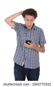 A young man holding his phone and putting a hand on the head surprised looking on his phone, isolated on a white background.