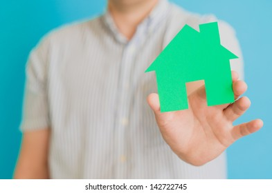 young man  holding a house
