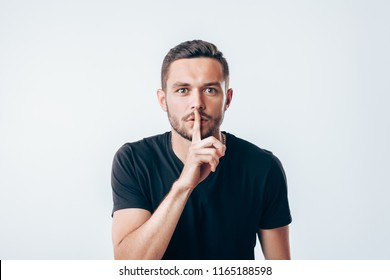 Young man holding index finger on lips asking for silence.  Secret concept