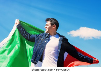 A Young Man Holding Italian flag Against the blue sky. toned image
