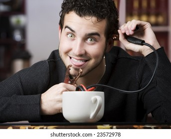 Young man holding jumper cables coming out of coffee mug