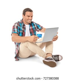 Young man holding laptop and credit card on white background