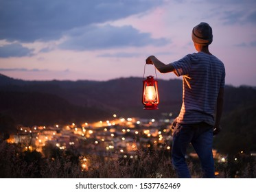 young man holding a lit old lamp