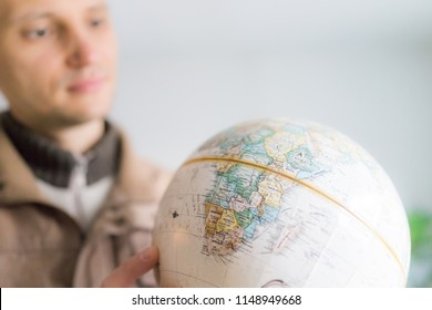 Young man holding looking at vintage retro old brown globe world map with equator, Africa continent