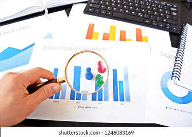A young man is holding a magnifying glass in his hand, looking at statistic figures - a business concept on the subject of sampling and selecting the right target group and examining it