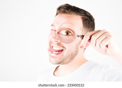 A Young Man Holding a Magnifying Glass to His Eye