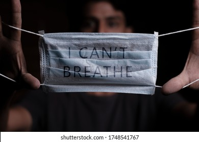Young man holding medical mask with I Can't Breathe inscription on it. Cooncept of Protest about racial discrimination of Black People in U.S. America