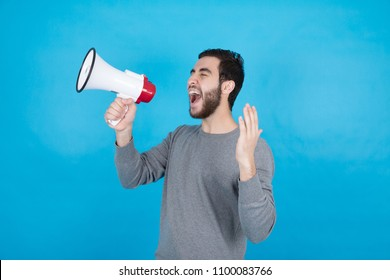 Young man holding the megaphone shouting over it in a side shot, on a blue background.