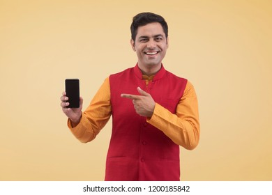 young Man holding mobile phone and pointing it