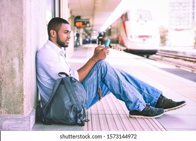 Young man holding mobile phone sitting at train station - Afro american student using smartphone waiting public tranport on railway platform - Lifestyle concept of transpotation , technology - Image
