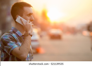 Young man holding mobile phone, using smartphone, making a call, talking on the phone, standing on sunny street with transport traffic on the background