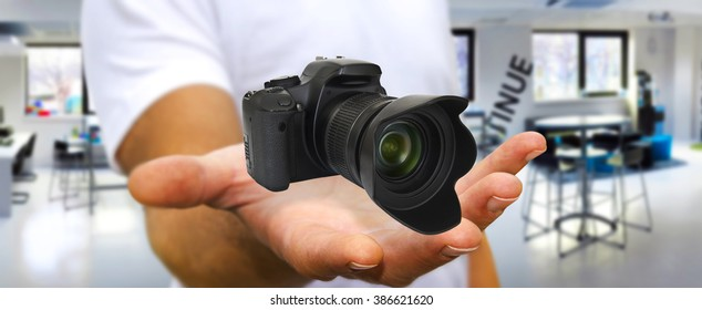 Young man holding modern digital camera in his hand