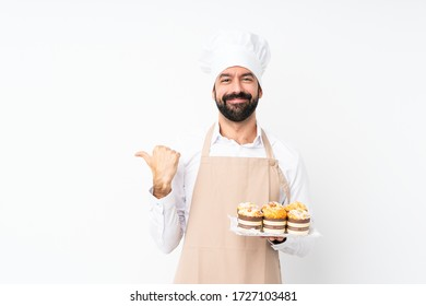 Young man holding muffin cake over isolated white background pointing to the side to present a product