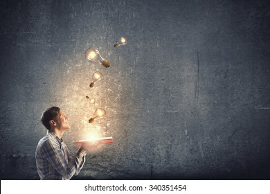 Young man holding opened book with glass glowing light bulbs flying out