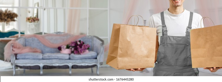 Young man holding paper bag, close-up. Wearing t-shirt, light grey background. Food delivery.