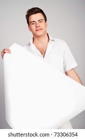 young man holding a paper. studio shot