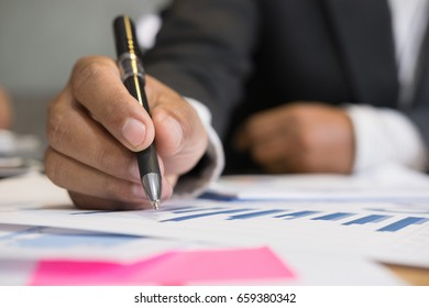 young man holding pen analyzing marketing graph in modern office. Businessman make a strategy plan at workplace. Business people working on table with financial chart
