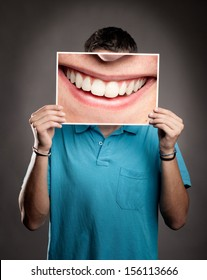 young man holding a picture of a mouth smiling