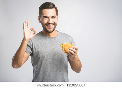 Young man holding a piece of hamburger. Student eats fast food. Hot helpful food. very hungry guy. Diet concept. Ok sign.