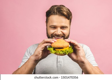 Young man holding a piece of hamburger. Bearded gyu eats fast food. Burger is not helpful food. Very hungry guy. Diet concept. Isolated over pink background.