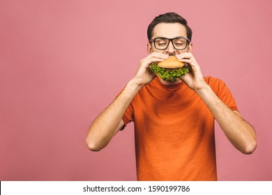 Young man holding a piece of hamburger. Student eats fast food. Burger is not helpful food. Very hungry guy. Diet concept. Isolated over pink background.