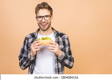 Young man holding a piece of sandwich. Student eats fast food. Burger is not helpful food. Very hungry guy. Diet concept. Isolated over beige background. Call me.