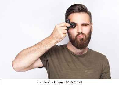 Young man holding and playing with fidget spinner. studio shot on white background.