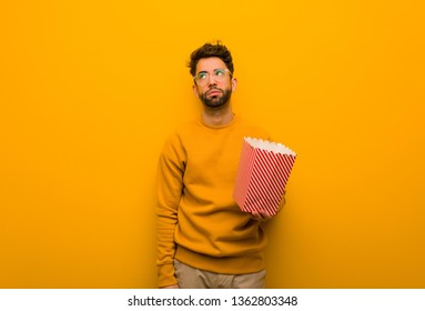 Young man holding popcorns tired and bored