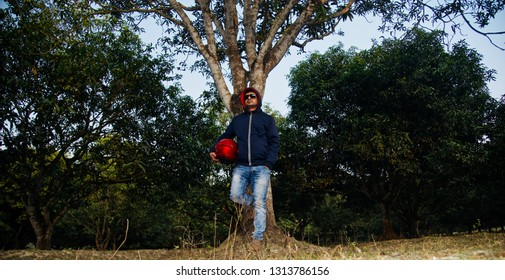 Young man holding a red bike helmet standing under a tree