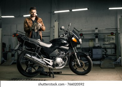 Young man holding a replacement part of a motorcycle. Man's hobbies cocept