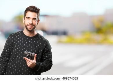 young man holding a retro camera