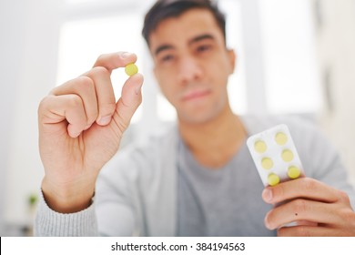 Young man holding round yellow pill