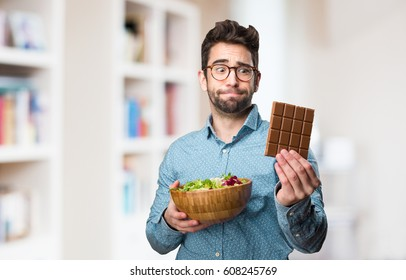 young man holding a salad and a chocolate bar
