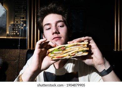 young man holding a sandwich in his hands.
