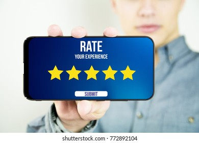 young man holding and showing a 5 stars ratingy full screen smartphone