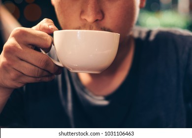 Young man holding sip drinking coffee cup in cafe at night