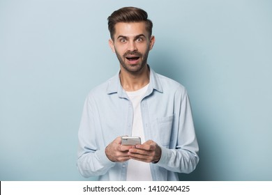 Young man holding smart phone look at camera open mouth feel stunned and surprised read unbelievable news in internet, get opportunity free cool application download, lottery win lucky moment concept