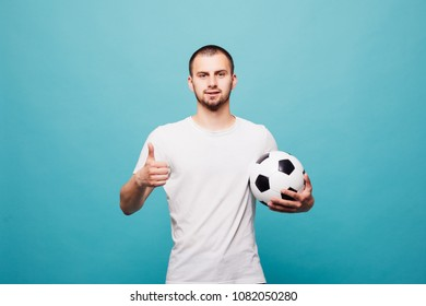 young man holding a soccer ball isolated on green background