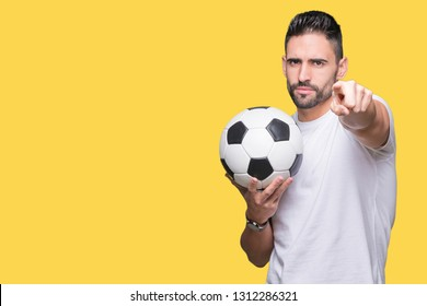 Young man holding soccer football ball over isolated background pointing with finger to the camera and to you, hand sign, positive and confident gesture from the front