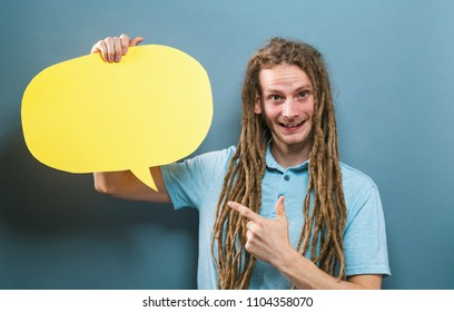 Young man holding a speech bubble on a solid background