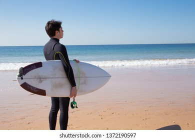 Young man holding surfboard and looking at sea. Handsome guy wearing wetsuit and standing on sunny beach. Surfboarding and tourism concept.