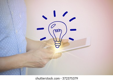 young man holding tablet computer with light bulb ,  social media concept , color filter image , business concept , business idea